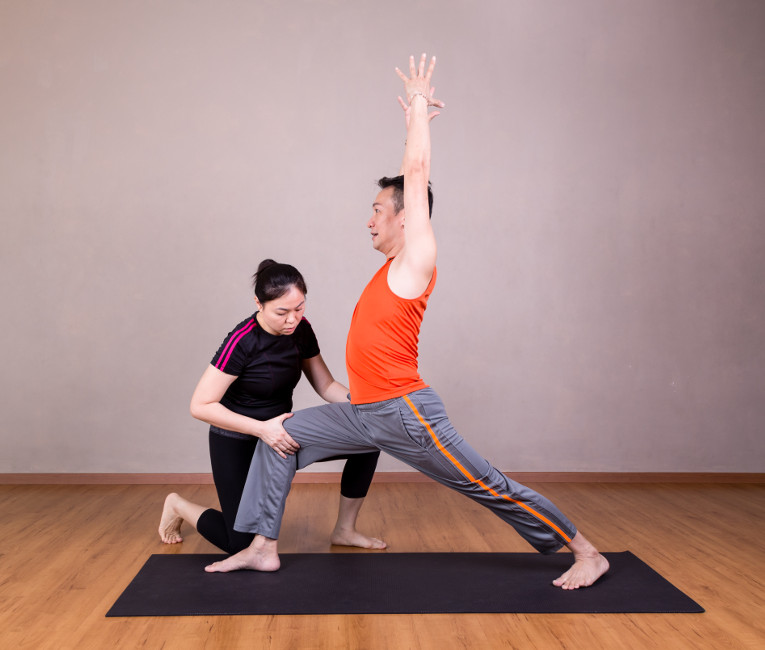 teacher of yoga for sport assisting a student with a yoga pose